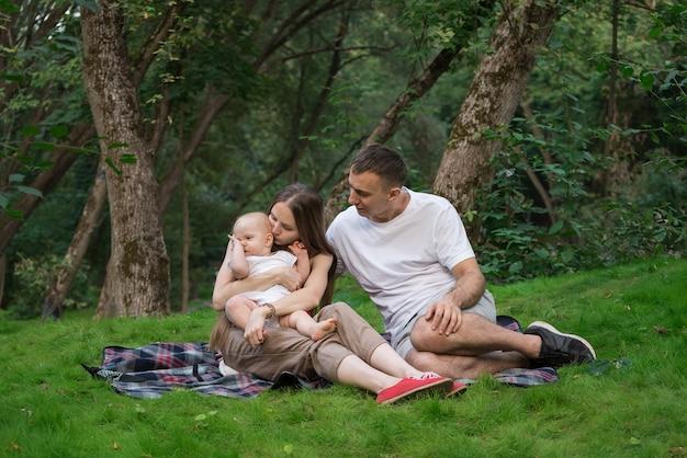 夏にピクニックをしている小さな子供を持つ若い親。ママのお父さんと赤ちゃんのピクニック毛布の上に座って