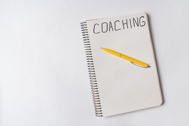 Коучинг, слово написанное на тетради, белая предпосылка. вид сверху блокнот и ручка. копировать пространство