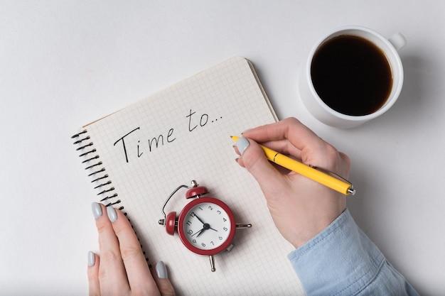 Рука женщины пишет в тетради надпись «время». блокнот и старинный будильник. планирование и кофе