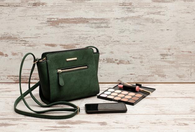 緑の女性のハンドバッグ、電話、アイシャドウパレット、口紅