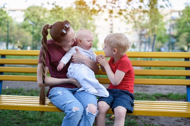 Молодая мама и двое детей на скамейке в парке
