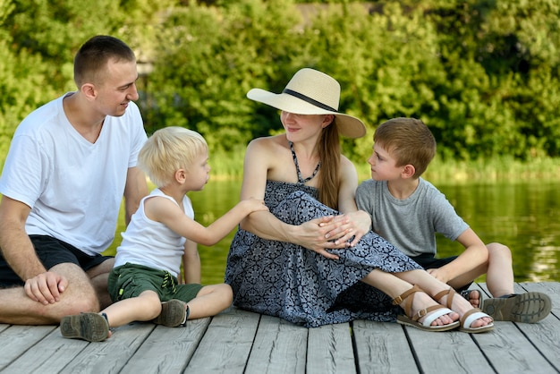 Счастливая молодая семья, папа-мама и двое маленьких сыновей сидят на речном пирсе