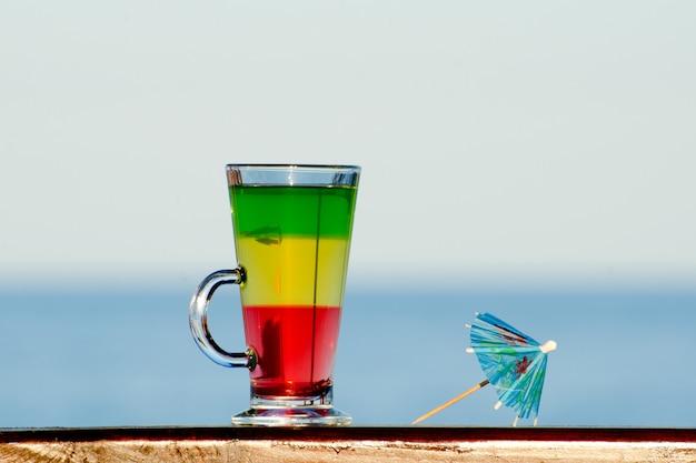 海の壁に色とりどりのカクテルが入ったグラス、カクテル用の傘