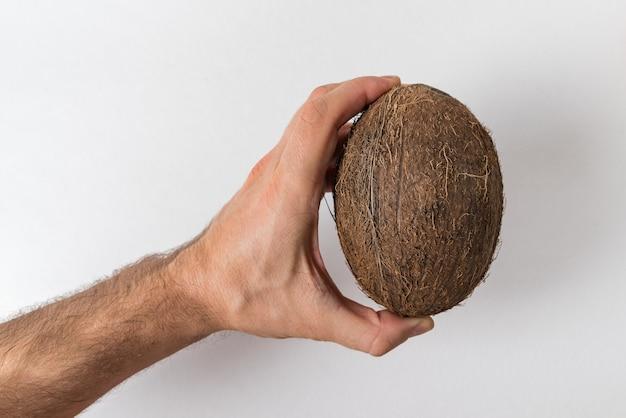 Мужская рука держит кокос на белой стене. концепция силы человека