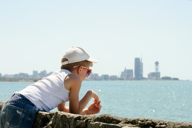 Мальчик в кепке смотрит на море. вид сбоку. город на расстоянии.