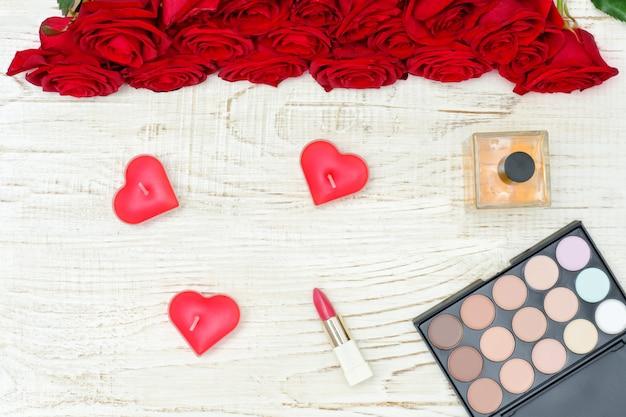 Букет из красных роз, свечей в форме сердца, парфюмерии, помады и палитры теней для век. белый деревянный стол. вид сверху