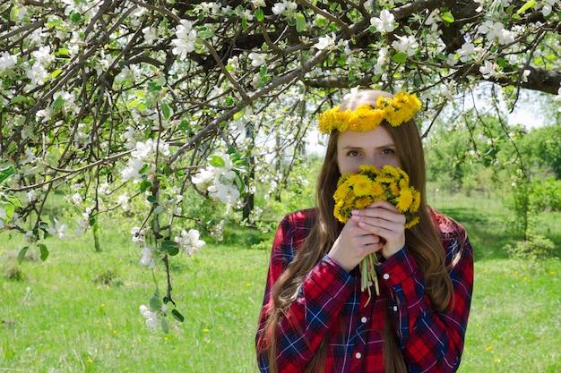 Девочка в венке из одуванчиков стоит под цветущей яблоней и нюхает букет