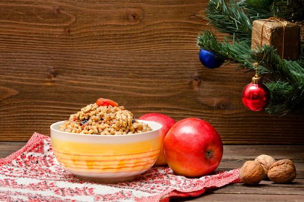 Блюдо из традиционных славянских угощений в канун рождества. рождественская елка, яблоки, грецкие орехи на узорчатой скатерти. коричневая деревянная стена. копировать пространство