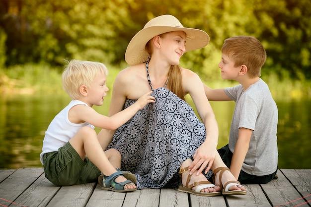 Красивая мама с двумя маленькими сыновьями сидят на пирсе на берегу реки