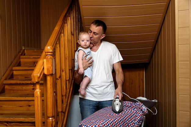 Отец с маленьким ребенком на руках гладил белье. делать работу по дому