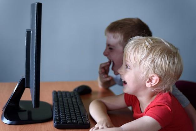 Два мальчика смотрят что-то на компьютер со смехом. детские развлечения
