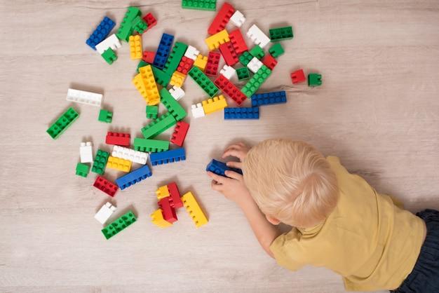 Белокурый мальчик, играя конструктор, лежа на полу. вид сверху