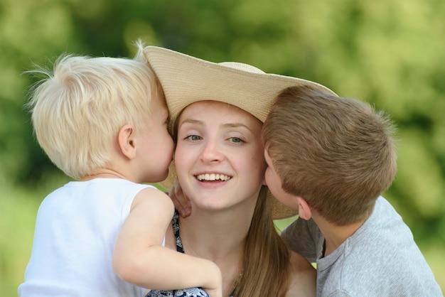 Два маленьких сына обнимают мать и целуют в щеку. крупный план