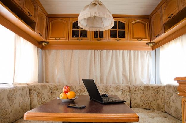 小さな居心地の良いキッチンのテーブルでフルーツの盛り合わせとスマートフォンでノートブックを開く