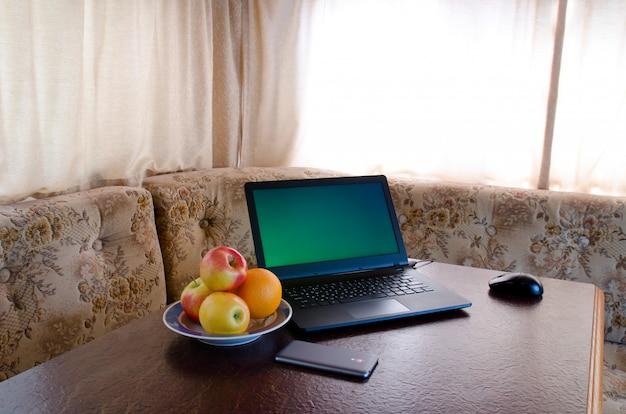 フルーツ、スマートフォンのプレートと居心地の良いキッチンでラップトップの側面図。ブレーク