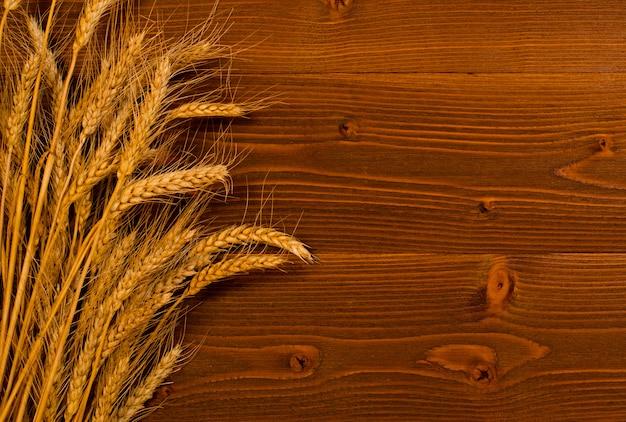 木材の背景に熟した小麦の耳