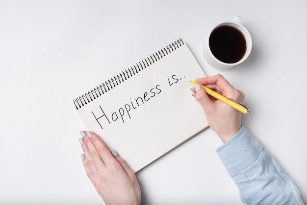 Тетрадь с текстом счастье. взгляд сверху женских рук писать в тетради, чашку кофе
