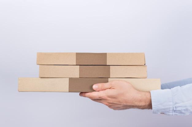 Коробки для пиццы в мужских руках. белый фон. вид сбоку. курьерская служба