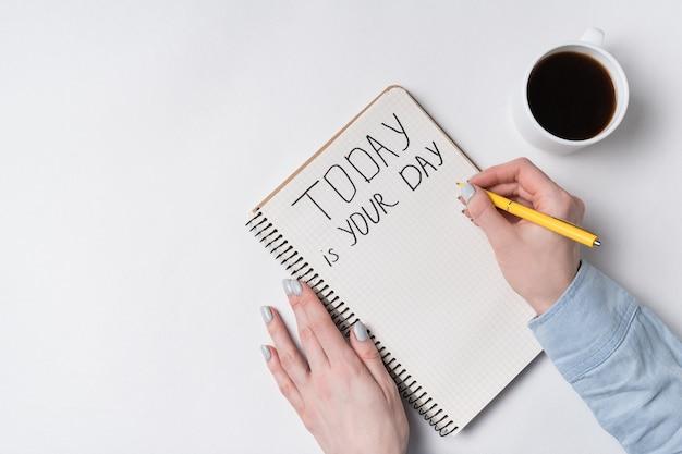 Мотивационная надпись сегодня - твой день. взгляд сверху сочинительства женщины в блокноте. утренний кофе