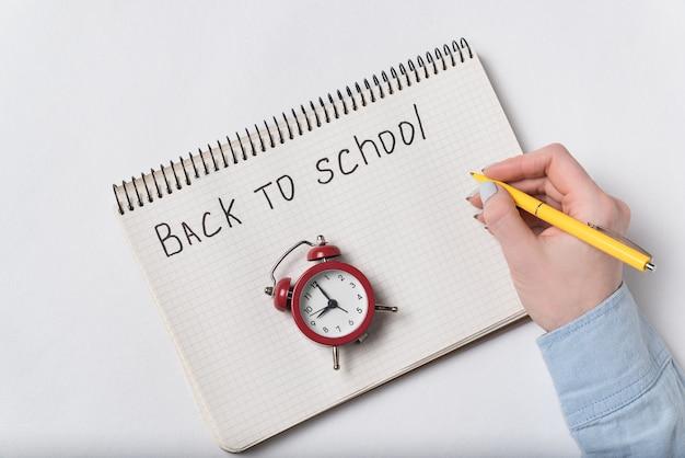 Женская рука пишет фразу назад в школу. старинный будильник. вид сверху