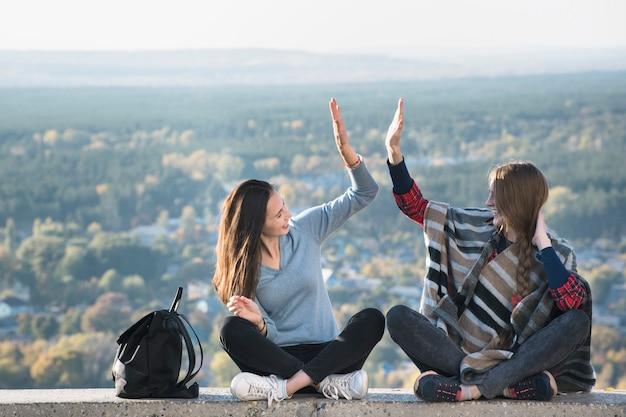 丘の上に座って楽しんで二人の笑顔の女の子。晴れた日