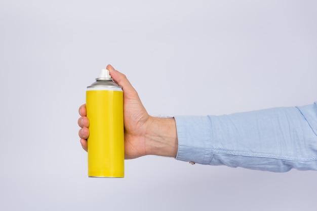 白い壁に黄色のスプレーボトルを持っている男性の手。コピースペース、モックアップ。側面図