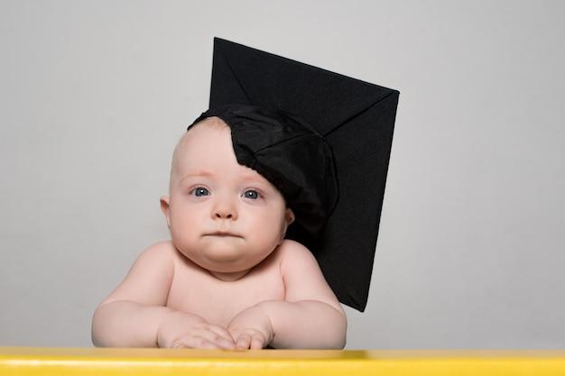 テーブルでアカデミックハットで深刻な赤ちゃんの肖像画。教育コンセプト