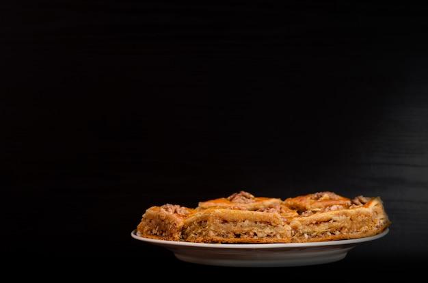 Тарелка с турецкой пахлавой мед на черном