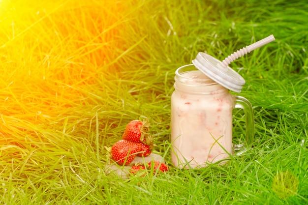 緑の芝生、日光の上のヨーグルトとイチゴのマグカップ