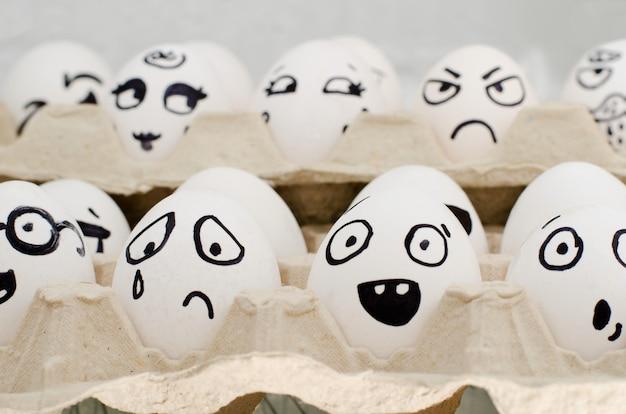 さまざまな感情で描かれたトレイの卵:悲しみ、驚き、驚き。閉じる