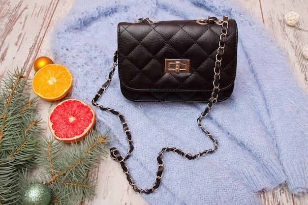 Концепция моды черная женская сумка на свитере, еловой ветке и оранжевом