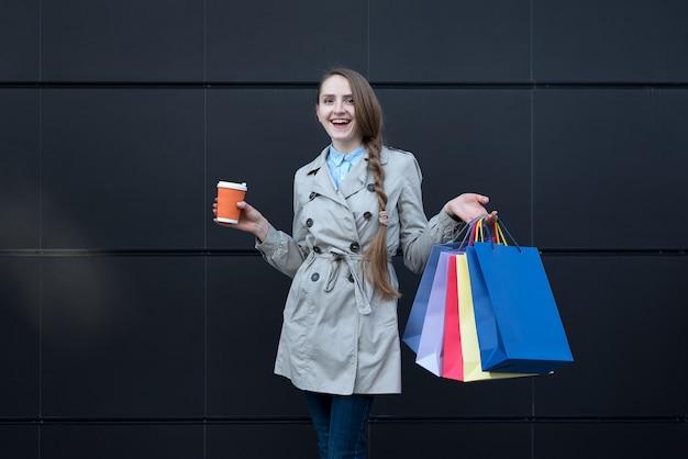 カラフルなバッグと紙コップを持つ幸せな若い女性。