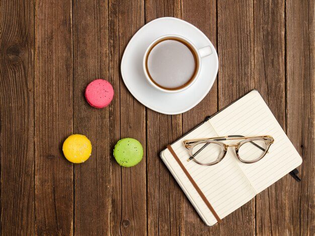 Кафе. блокнот, стаканы, кофейная кружка и десерт