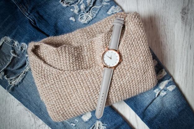 Стильные часы на свитере и рваные джинсы.