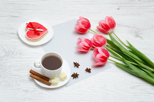 ピンクのチューリップ、コーヒーのマグカップ、赤いジンジャーブレッド。