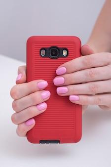 優しいピンクのマニキュア。スマートフォンで女性の手