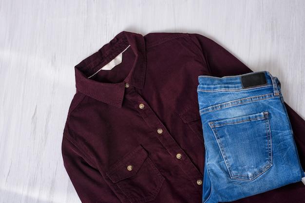 マルーンコーデュロイシャツとブルージーンズの木製