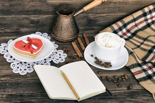 カプチーノ、ハート型のクッキーの幅のメッセージ、ノート、鉛筆、コーヒーのカップ