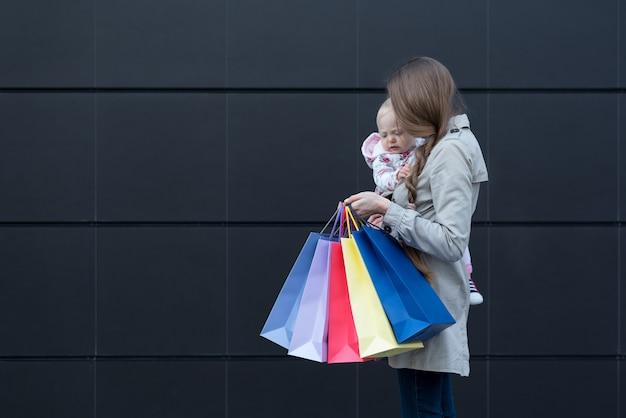 腕と買い物袋を手に小さな娘を持つ若い母親。