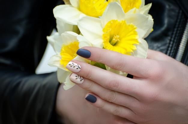 水仙を保持している若い女性の手