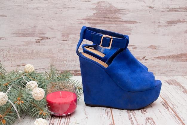 青いスエードの靴、モミの枝、ガーランド、キャンドル。ファッションコンセプト