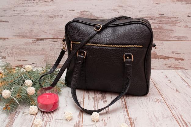Черная сумка, еловая ветка, гирлянда и свеча. концепция моды