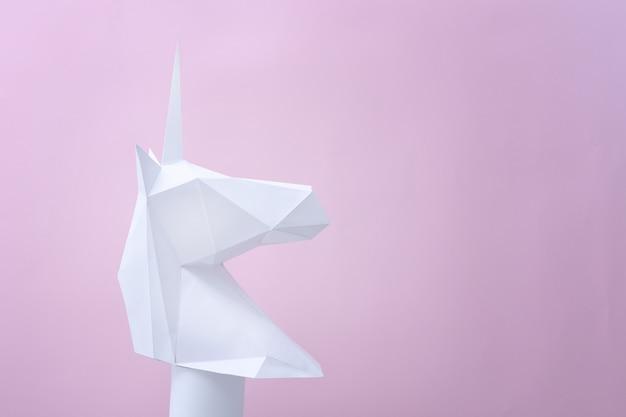 Единорог белой бумаги на розовом фоне.