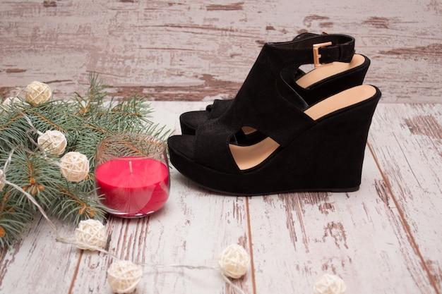 Черные замшевые туфли, еловая ветка венка и свеча. концепция моды