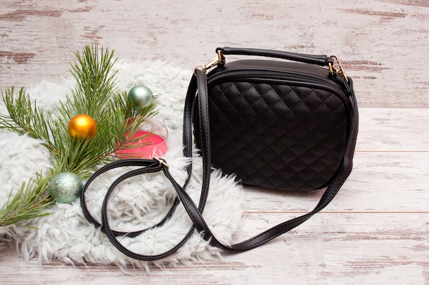 小さな黒い女性のハンドバッグ、装飾品、モミの枝、キャンドル。ファッションコンセプト