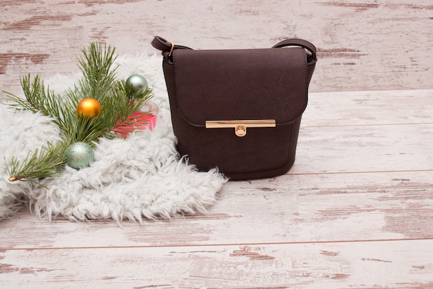 Маленькая коричневая женская сумочка, еловая ветка с украшениями. концепция моды