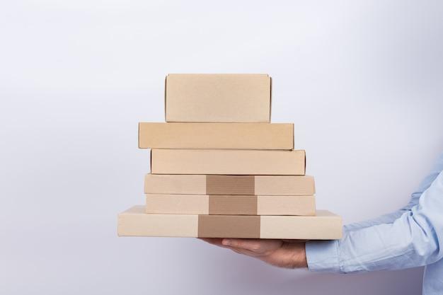 Работник доставляющий покупки на дом держа картонные коробки на белой предпосылке. быстрая доставка