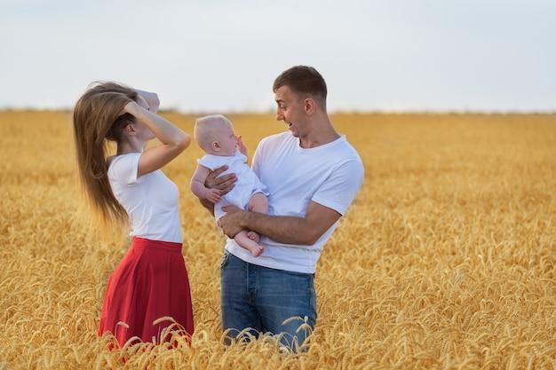 Молодая пара с ребенком в пшеничном поле. мама папа и ребенок веселятся в сельской местности