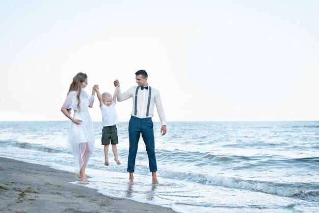 Молодые родители с сыном гуляя на пляж. мама и папа, взявшись за руки ребенка. счастливое родительство