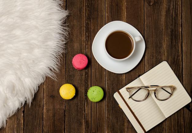 コーヒーマグカップ、マカロン、ノートブック、木製テーブルの上のグラス。上面図
